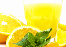 Orange juice. Orange halves in front of a tumbler with orange juice, decorated with mint leaves Royalty Free Stock Photos
