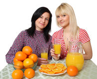 Orange juice. Two young women with fruit, a white background Royalty Free Stock Photography