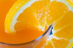 Orange juice. Real macro off an orange and the glass with juice Royalty Free Stock Photo