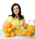 Orange juice. The young woman behind a table with fruit on a white background Stock Image
