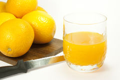 Orange juice. Oranges and orange juice in a glass Royalty Free Stock Photo