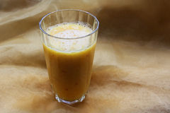 Orange juice. A glass of orange juice on yellow cloth Stock Images