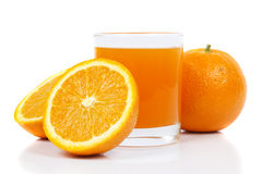 Orange juice. Glass of freshly squeezed orange juice with half an orange on a white background with reflectin Royalty Free Stock Images