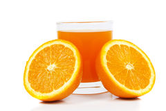 Orange juice. Glass of freshly squeezed orange juice with half an orange on a white background with reflectin Royalty Free Stock Image