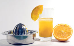 Orange juice. Half an orange with a glass of orange juice and an old-fashioned squeezer royalty free stock image