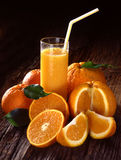 Orange_juice. Orange juice in glass with oranges on wooden background Royalty Free Stock Images