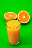 Orange juice. A tall glass of orange juice with oranges around it Royalty Free Stock Photos