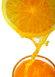 Orange juice. Pouring orange juice from orange, isolated background with clipping path Stock Photos