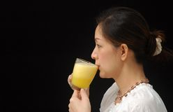Orange Juice. Beautiful Chinese lady drinking orange juice, isolated black background stock photos