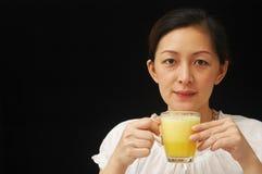 Orange Juice. Beautiful Chinese lady drinking orange juice, isolated black background stock photography