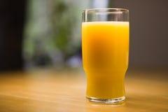 Orange Juice. Glass of orange juice on a wooden kitchen table Stock Photography