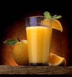 Orange juice. In wet glass on wood with garnish Royalty Free Stock Images