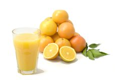 Orange juice. A glass of orange juice in foreground and blurred oranges in background Royalty Free Stock Photo