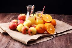 Orange juice and apple juice with apples and oranges on wooden table Royalty Free Stock Photos
