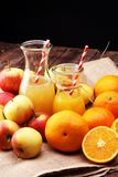 Orange juice and apple juice with apples and oranges on wooden table Stock Image