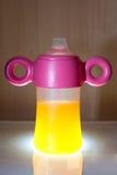 Orange juice baby bottle Stock Images
