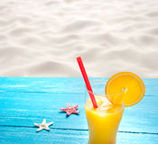 Orange juice at the beach Royalty Free Stock Photography