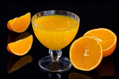 Orange juice on black background, decorated with orange fruits. Horizontal shot Royalty Free Stock Photo