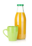Orange juice bottle and green cup Royalty Free Stock Photo