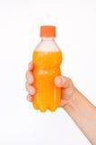 Orange juice bottle in hand Stock Photography