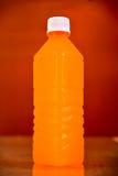 Orange juice bottle. Isolated on brown background Royalty Free Stock Image