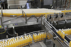 Orange juice bottles on conveyor belt in bottling plant Royalty Free Stock Images