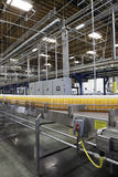 Orange juice bottles on conveyor in bottling plant Stock Images