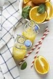 Orange juice in bottles and oranges top view Stock Photos