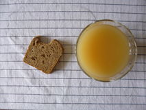 Orange juice and bread on plaid textile tablecloth Stock Image