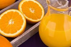 Orange juice in carafe with oranges Royalty Free Stock Images
