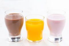 Orange juice, chocolate milk and fruit yoghurt on white table Royalty Free Stock Photo