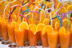 Orange juice cocktail. Lots of Orange juice cocktails with colored straws ready to served  at a summer party Stock Photos