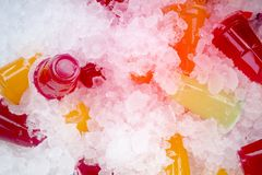 Orange juice and colorful sweet water on ice crystals stock image
