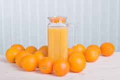 Orange juice beside delicious ripe oranges on the table Stock Photo