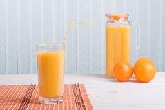 Orange juice beside delicious ripe oranges on the table Stock Images