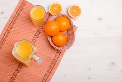 Orange juice beside delicious ripe oranges on the table. Orange juice beside delicious ripe oranges  the table Stock Image