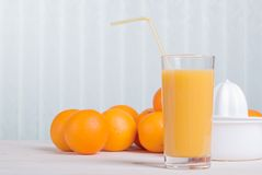 Orange juice beside delicious ripe oranges on the table. Orange juice beside delicious ripe oranges the table Stock Photo
