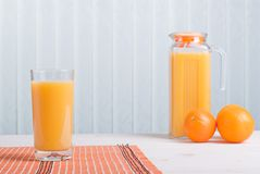Orange juice beside delicious ripe oranges on the table. Orange juice beside delicious ripe oranges on table Stock Photography