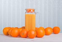 Orange juice beside delicious ripe oranges on the table. Orange juice beside delicious ripe oranges the table Royalty Free Stock Photo