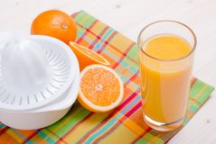 Orange juice beside delicious ripe oranges on the table. Orange juice beside delicious ripe oranges the table Royalty Free Stock Photos