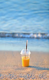 Orange juice in a disposable cup in the sand on the beach Royalty Free Stock Photography