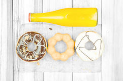 Orange juice and doughnut. Set of doughnuts and bottle of orange juice put on white wood table, feeling sweet, hangry, and thirsty royalty free stock photos