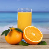 Orange juice drink and oranges on the beach and sea Royalty Free Stock Image