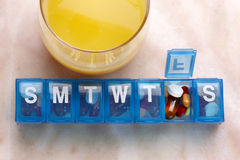 Orange juice with daily  drug organizer Stock Photography