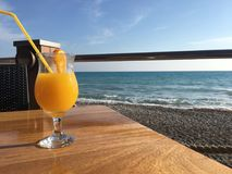 Orange juice. Exotic concept of an orange juice with sea background Royalty Free Stock Photography