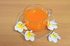 Orange juice with flowers on wooden table Stock Photography