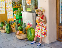 Orange juice. Girl with a glass of juice on the street outside the shop Stock Photography