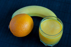 Orange juice in glass, fresh fruits on a black Stock Images