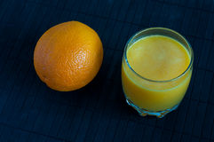 Orange juice in glass, fresh fruits on a black Royalty Free Stock Images