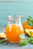 Orange juice in glass and fresh fruits with leaves on wooden background Stock Photo
